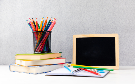 colorful pencils with books and chalkboard on a desk with gray background and copyspace