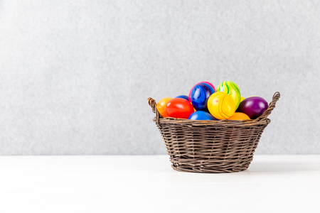 colorful easter eggs in a basket with gray background and copyspace Reklamní fotografie