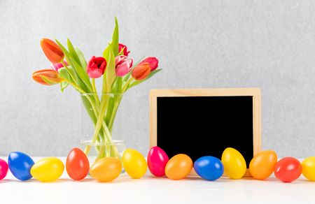 colorful tulips with chalkboard and easter eggs on a gray background