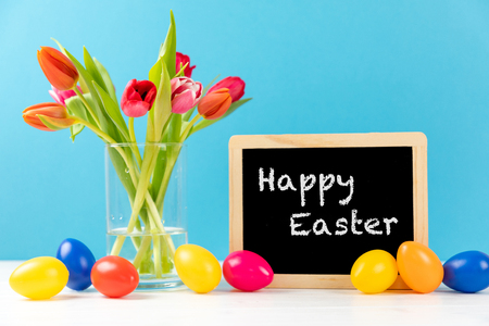 colorful tulips with chalkboard and easter eggs on a blue background with text happy easter