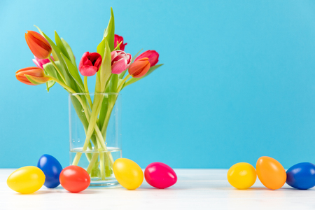 colorful tulips in a vase with colored easter eggs and copy space