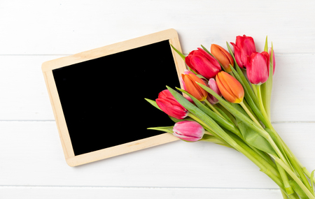 colorful tulips with chalkboard with copy space and white background