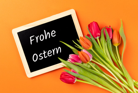 colorful tulips with chalkboard and orange background with german text frohe ostern, in english happy easter