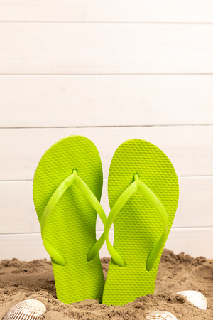 flip flops with sand and shellfish with white wooden background and copyspace