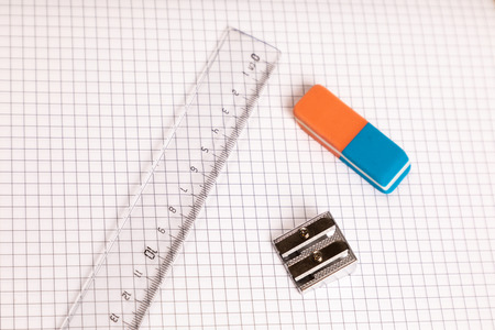 school equipment ruler, eraser with checkered paper