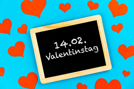chalkboard with red love hearts on a blue background with german text 14.02. Valentinstag, in english 14.02. valentines day
