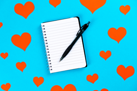 paper with pen on a blue background with red hearts