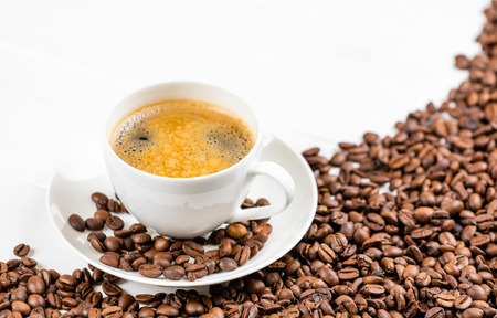 coffee cup with coffee beans on a white wooden background