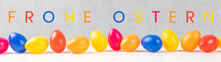 colorful easter eggs with gray background and german text frohe ostern, in english happy easter