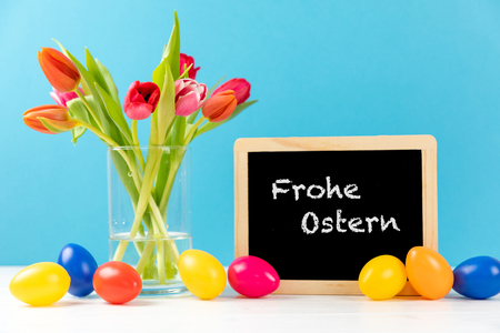 colorful tulips with chalkboard and easter eggs on a blue background with german text frohe ostern, in english happy easter