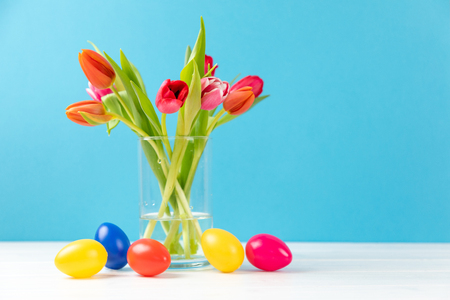 Coloridos tulipanes en un jarrón con huevos de pascua de colores y copie el espacio Foto de archivo