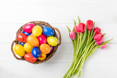 easter nest with colorful eggs and tulips on a white background