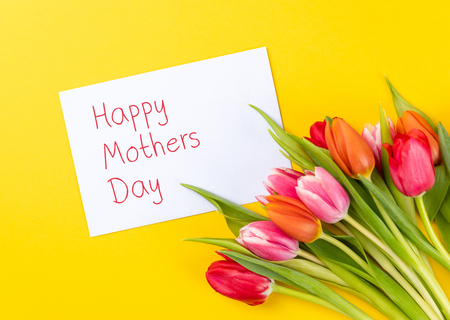 colorful tulips on a yellow background with white paper and text happy mothers day