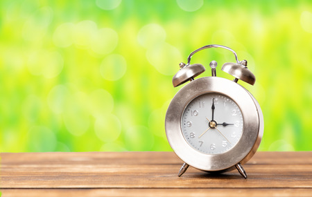 clock for summer time change with copy space with green garden background