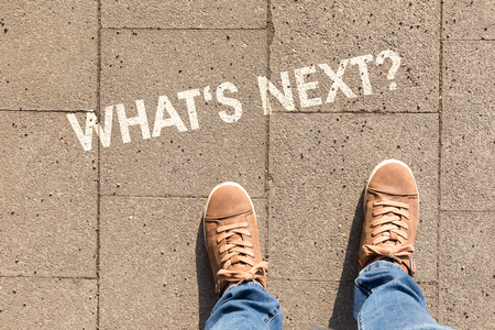 shoes on asphalt with text whats next?