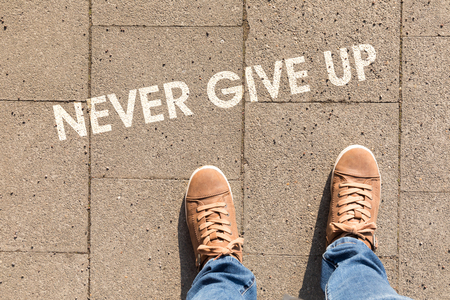 shoes on asphalt with text never give up Stock Photo