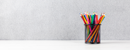 colorful pens in a quiver on a desk with gray background