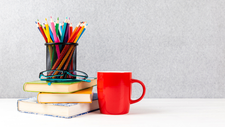 books, colorful pencils, glasses and red cup on a desk with gray background