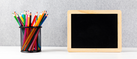 colorful pencils and chalkboard on a desk with gray background and copyspace