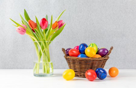 colorful tulips in a Vase with easter eggs in a basket with gray background