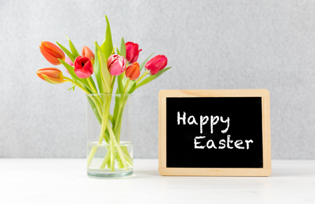 colorful tulips in a Vase with gray background and chalkboard with text happy easter