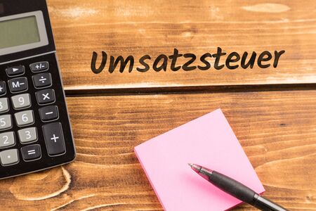 business desk with paper, pen and calculator and german text Umsatzsteuer, in english value added tax