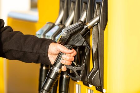 Hand with fuel nozzle at a gas station