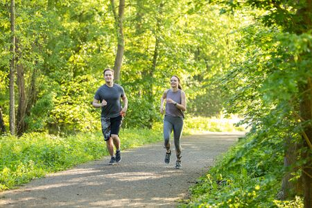 young woman and man running in a forest and making fitness workout