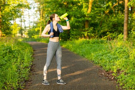 Young jogger with a towel and drinking bottle in nature