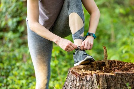 Young woman makes fitness and ties shoelaces in nature