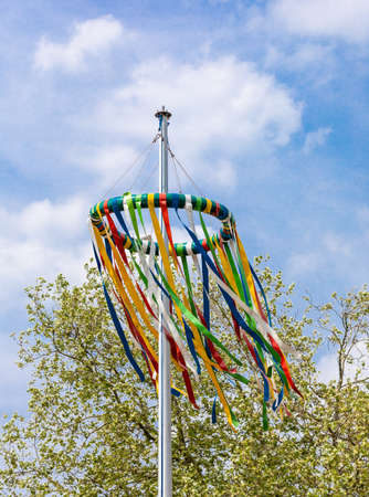 tradiotional maypole with blue sky in may