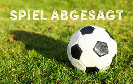 black white soccer ball lying on grass and german text spiel abgesagt, in english game canceled