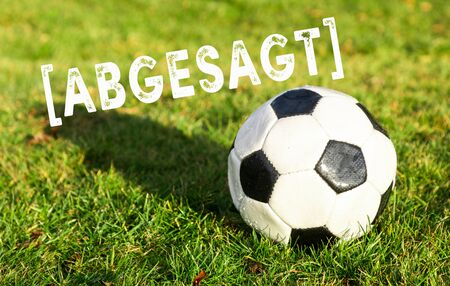 black white soccer ball lying on grass and german text abgesagt, in english canceled