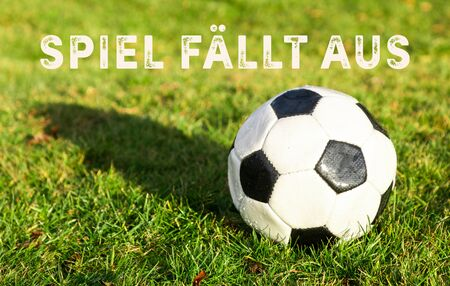 black white soccer ball lying on grass and german text spiel fällt aus, in english game fails