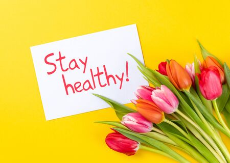 colorful tulips on a yellow background with text stay healthy Banque d'images