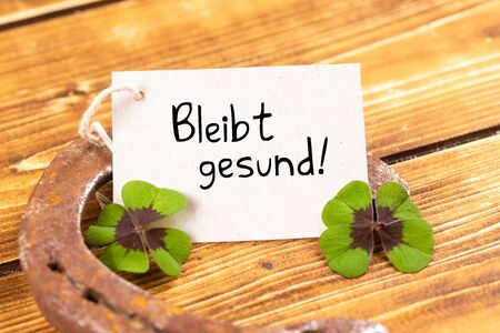 horseshoe with green shamrock sign for luck and german text bleibt gesund, in english stay healthy