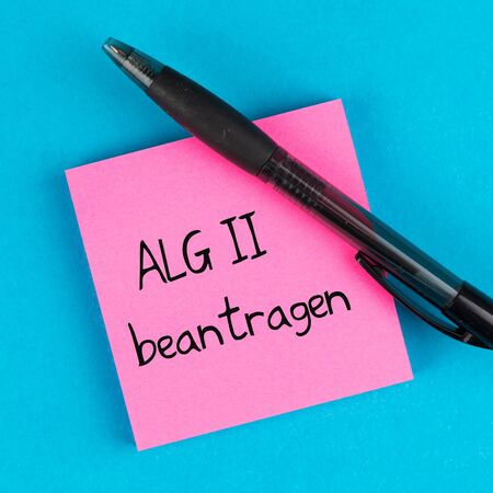 pink paper with pen on blue background and german text ALG II beantragen, in english apply for unemployment benefits