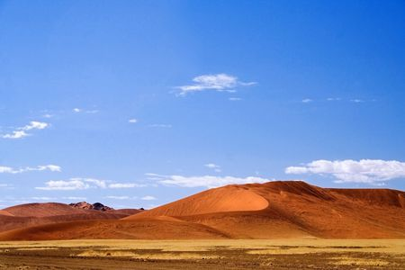 Desert landscape  with red dunes and blue sky with few wispy clouds and yellow grass in the foreground in Namibia