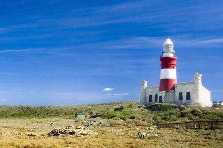 アガラス岬、南アフリカ共和国で明るい日光の下草原の灯台 写真素材