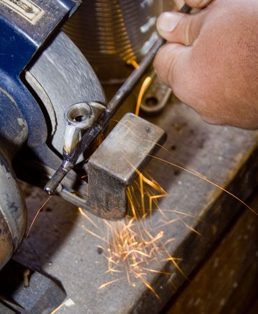 man grinding metal rod with sparks flying photo