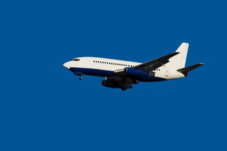 passenger jet in flight against clear blue sky with landing gear down Stock Photo