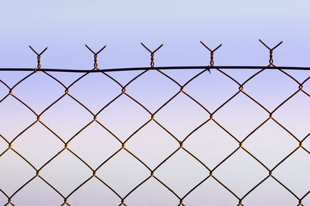 wire fence: top of wire fence against soft dusk sky Stock Photo