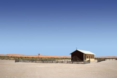 remote church in namib desert with clear blue sky and red dunes in background