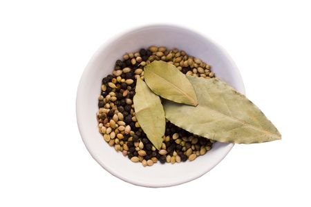 three bay leaves,coriander seeds and blackpeppercorns in  porcelain bowl isolated on white background with clipping path photo