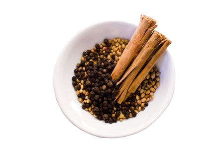 coriander seeds, black peppercorns and two cinnamon sticks in white porcelain bowl on white background Stock Photo