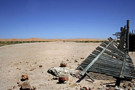 desert landscape with broken wooden picket fence in the foreground,dunes and blue sky in background in namibia photo