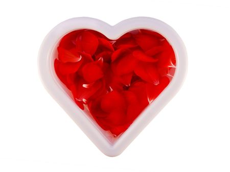 heart shape cookie cutter filled with red flower petals on white background  photo