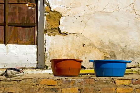 red and blue wash basins on the porch of an old derelict building