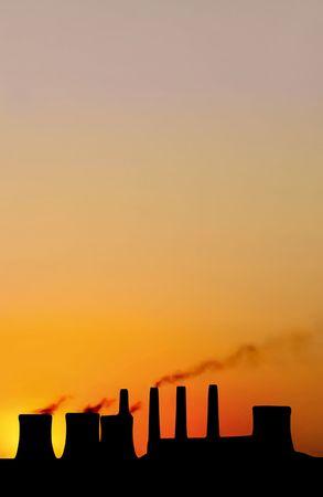 black silhouette of power station against dusk sky
