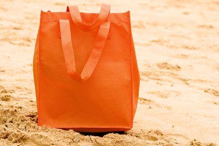 orange beach bag on sand
